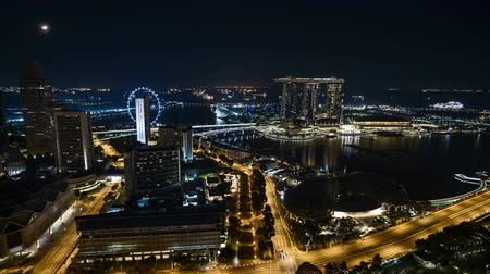 Time lapse of night scene at Singapore city with moon rise. Pan left