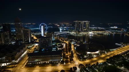 Time lapse of night scene at Singapore city with moon rise. Tilt up Vídeos