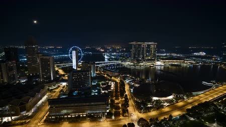 Time lapse of night scene at Singapore city with moon rise. Tilt down
