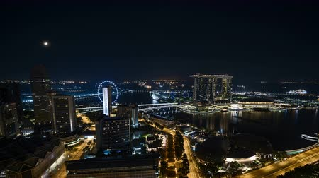 Time lapse of night scene at Singapore city with moon rise. Zoom out Vídeos