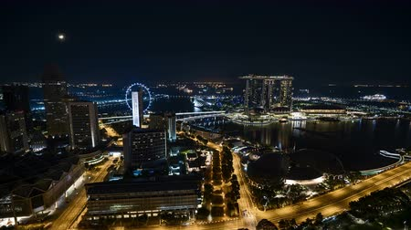 Time lapse of night scene at Singapore city with moon rise. Zoom in