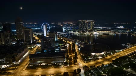 Time lapse of night scene at Singapore city with moon rise.