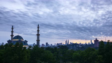 4k UHD time lapse of sunrise over silhouette mosque at Kuala Lumpur city skyline. Pan left Vídeos