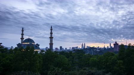 4k UHD time lapse of sunrise over silhouette mosque at Kuala Lumpur city skyline. Tilt down Vídeos