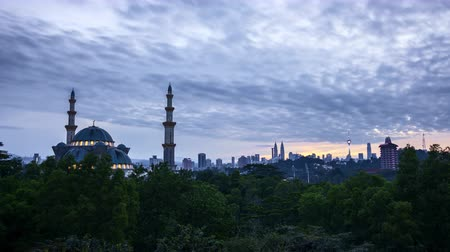 4k UHD time lapse of sunrise over silhouette mosque at Kuala Lumpur city skyline. Zoom out