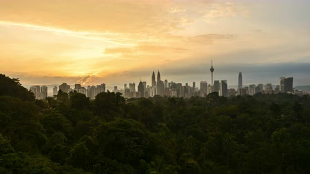 4k time lapse of clear sunrise from Kuala Lumpur city skyline. Pan left