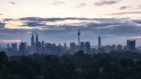 4k time lapse of clear sunrise from Kuala Lumpur city skyline. Tilt down
