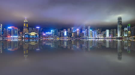 4k time lapse of night scene at Hong Kong city skyline during daily light show, with reflection effect. Pan left Vídeos