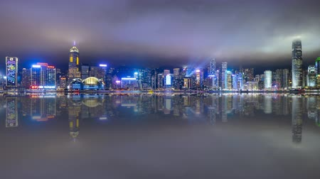 4k time lapse of night scene at Hong Kong city skyline during daily light show, with reflection effect. Pan right