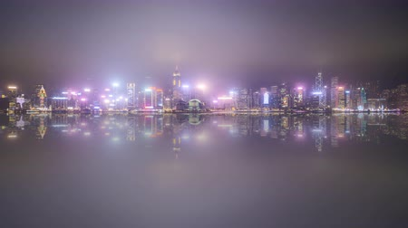 4k time lapse of sunset day to night at Hong Kong city skyline during cloudy and misty weather.  Pan left