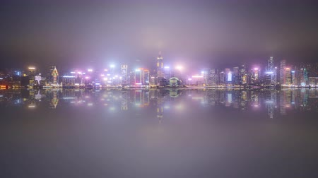 victoria : 4k time lapse of sunset day to night at Hong Kong city skyline during cloudy and misty weather. Pan right