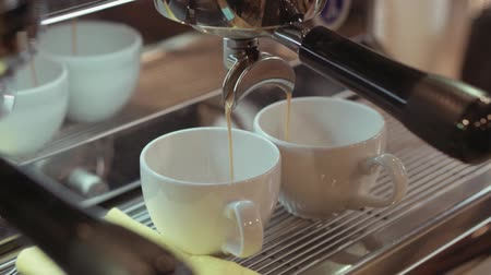 kitchen paper : Rotation, close up view of a silver coffee machine pouring hot, fresh coffee in two white cups. An espresso machine brewing a hot coffee into white cups. Cafe bar settings on the background. Stock Footage