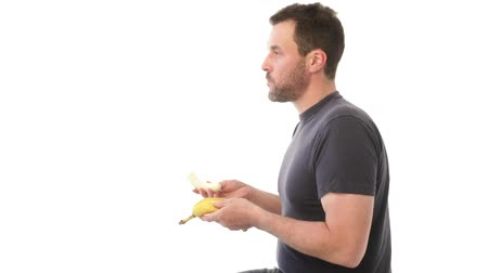 muz : Mature man eating a banana, throwing peel away Stok Video