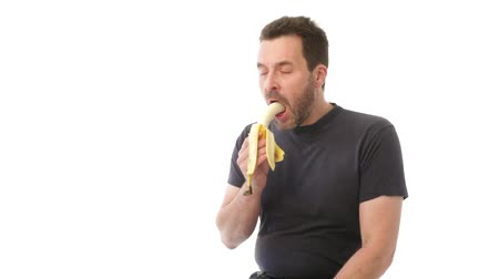 jeść : Mature man eating a banana, throwing peel away Wideo