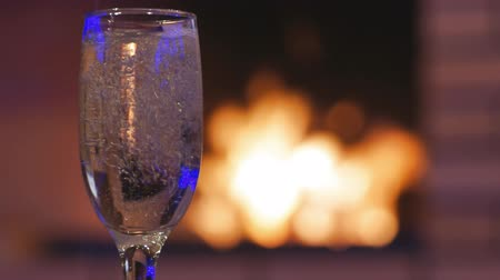 emanações : Glass of sparkling wine and fireplace in bokeh
