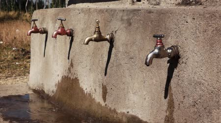 засуха : Water point with faucets at school in africa with dripping water Стоковые видеозаписи