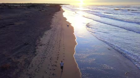 Aerial panning with drone on young attractive man jogging on the beach at sunrise. Running workout in fitness and healthy lifestyle concept. Стоковые видеозаписи