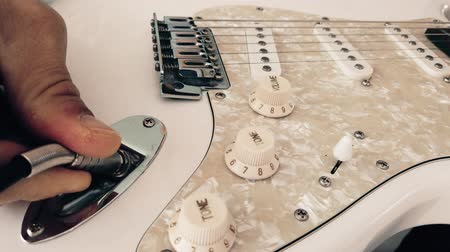 Close up of guitarists hand plugging audio cable in electric guitar