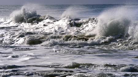 Waves breaking near shore, with the sun shining on them