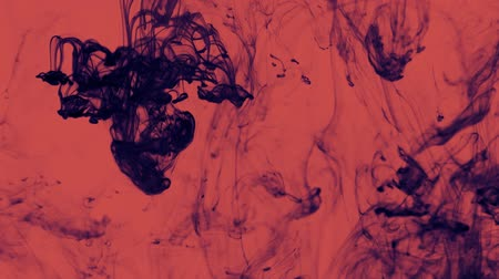 Dark blue liquid swirls over red Wideo