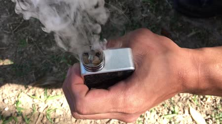 sigara : showing burn of e juice or e liquid in the coil, wire and cotton inside the atomizer of electronic cigarette for vaping, close up scene