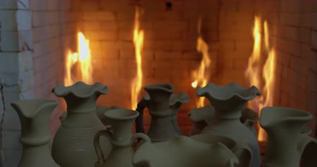louça de barro : Camera tracks pushcart full of clay jugs enters in to oven full of fire for roasting. Stock Footage