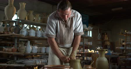 jarro : Potter rises a clay jug on a spinning wheel.