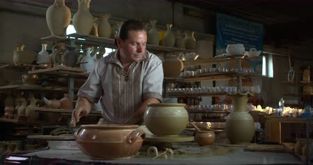 oleiro : Potter cuts clay jug from spinning wheel with a string then takes it off and puts on a clay plate.