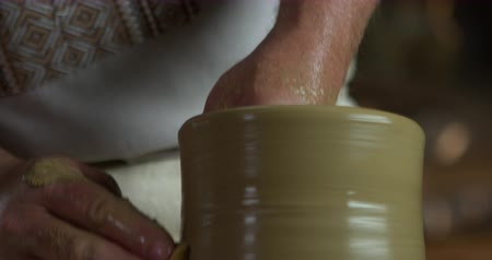 louça de barro : Tilting shot of potters hands rising clay jug and starting to shape it.