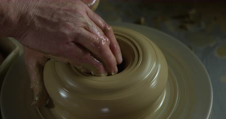 louça de barro : Close up shot of potters hand starting to produce a clay jug on a spinning wheel. Stock Footage