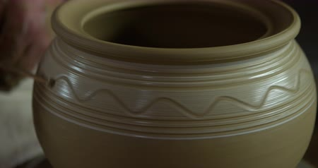 louça de barro : Potter draws ornaments on a white color stripe of a finished clay jug.