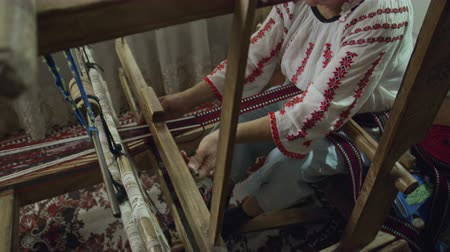 мини : A hand-held medium shot of weaver who is weaving a traditional belt on a obsolete wooden weaving machine.