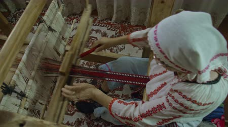 ozdobnik : An overhead pan shot of weaver who is weaving traditional belt on a obsolete wooden weaving machine.