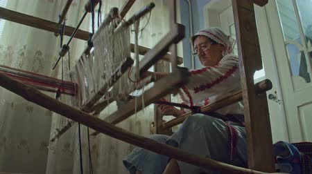 wełna : A low angle shot of weaver who is weaving a traditional belt on a obsolete wooden weaving machine.