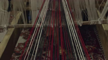 vesszőfonás : A tilting shot of threads and pedals of an obsolete wooden weaving machine while being in use by a weaver.