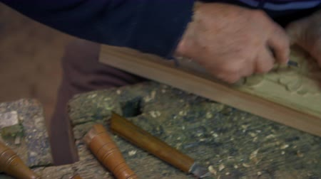 chisel : Overhead pan from a set of chisels to a wood carver who carves leaves and flowers on an oak plank.