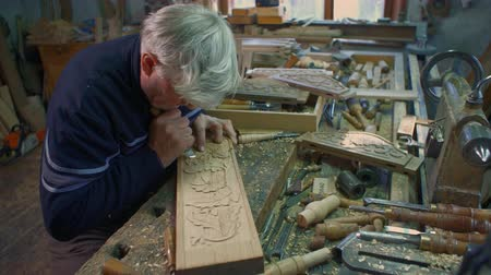 лесоматериалы : Medium hand-held shot of wood carver who is carving an oak plank on his table in the workshop.