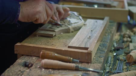 chisel : Wood carver is carving an oak plank on his table in the workshop.