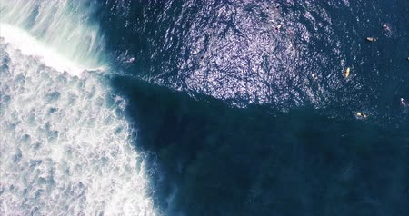 вид сверху : Aerial shoot of the sea waves with foam and surfers, Bali. Camera hangs over the waves