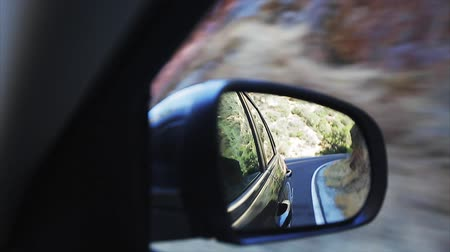Reflection of the road in the mountains in the wing mirror