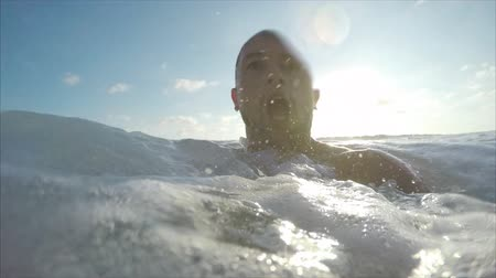 Man hardly swims in the sea with powerful waves