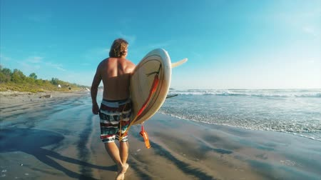 Surfer walks on the beach with board
