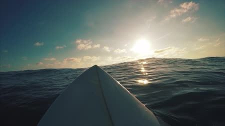 Surfer wating wave in the ocean. POV with surfboard view
