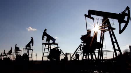 pompki : working oil pumps silhouette against sun