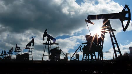 oil industry : working oil pumps silhouette against timelapse clouds Stock Footage