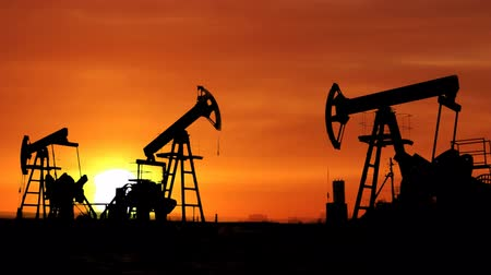 rigs : working oil pumps silhouette against timelapse sunrise