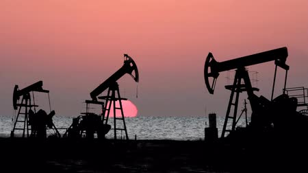 pompki : working oil pumps silhouette against sunrise