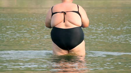nadváha : woman with overweight bath in river
