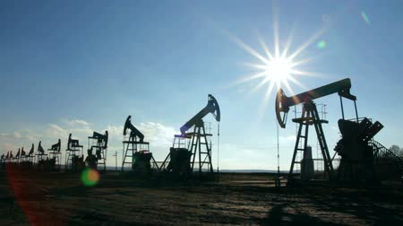 natural resource : working oil pumps silhouette against sun