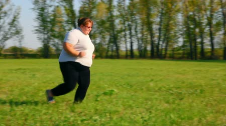 потеря : sport - overweight woman running on green meadow Стоковые видеозаписи